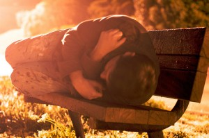Homeless person sleeping on a park bench.